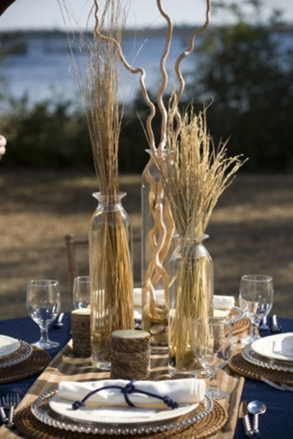 a navy tablecloth, wheat and driftwood, woven placemats, cadles wrapped up with birch bark