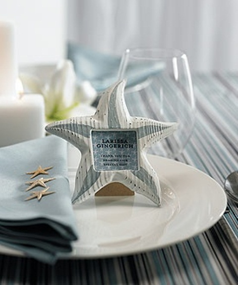 a light blue and white place setting with a starfish name holder, a striped tablecloth, a light blue napkin and candles