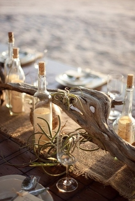 a burlap table runner with driftwood, air plants, bottles and simple glasses and porcelain for a neutral and natural beach tablescape