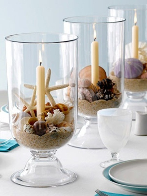 a beach tablescape with large glasses filled with sand, seashells and starfish, candles and blue plates and napkins