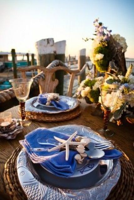 a bright beach tablescape with woven placemats, blue fish plates, blue napkins with starfish napkin rings plus a large neutral bloom centerpiece