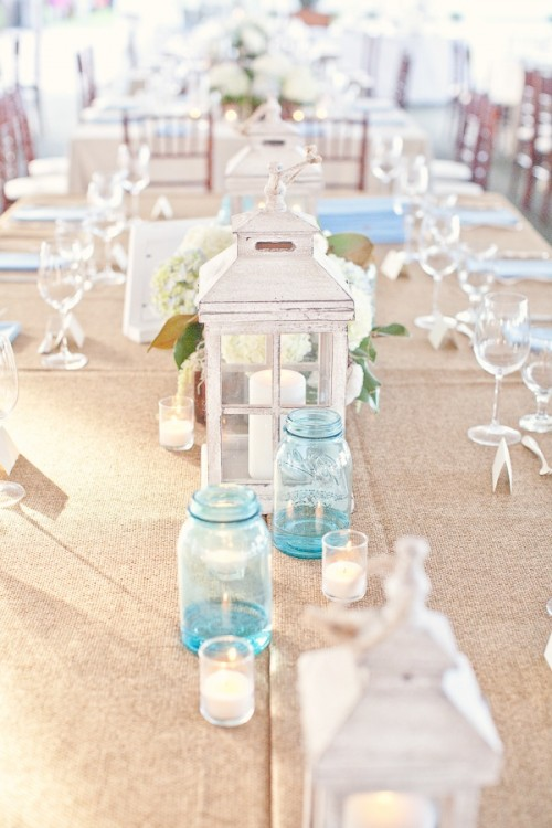a neutral beach tablescape with a neutral tablecloth, a white candle lantern, blue candle holders and a white hydrangea centerpiece