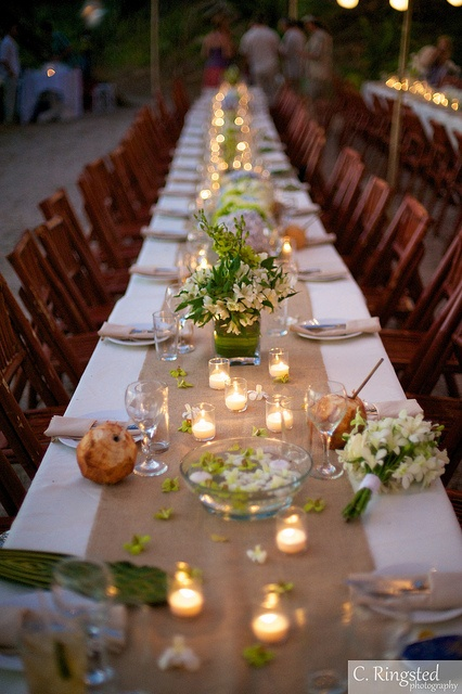a chic tropical wedding table with a neutral table runner, white blooms and greenery, candles plus floating flowers