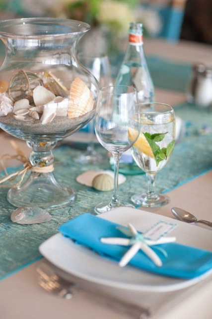 a light blue wedding tablescape with a blue runner and napkins, a jar with sand and seashells, starfish napkin rings and seashells right on the table