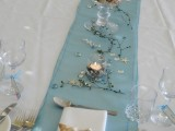 a beach tablescape with a blue runner, twigs, starfish, a glass with seashells and candles plus neutral napkins