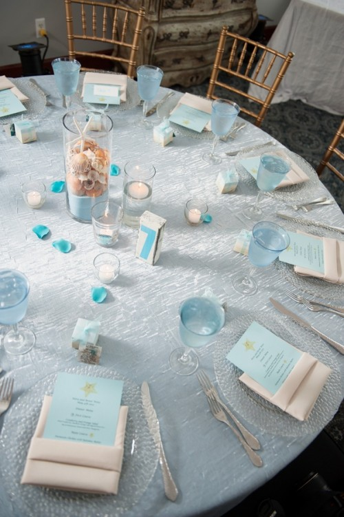 a light blue wedding tablescape with a tablecloth with a sparkle, forsted glass plates and blue menus plus a centerpiece of a tall glass with sand, seashells and a starfish
