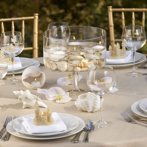 a neutral wedding tablescape with a tablecloth, seashells, white blooms, neutral napkins and mini sand castles as favors