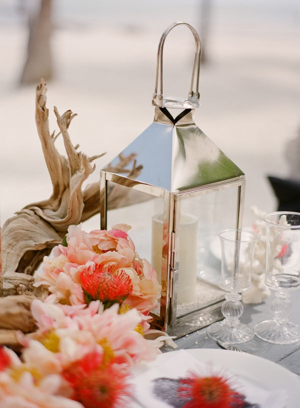 an uncovered table with driftwood, bright tropical blooms, a candle lantern and corals