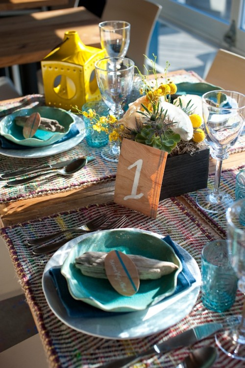 a colorful beach wedding tablescape with woven placemats, blue plates, glasses, a centerpiece with succulents and air plants