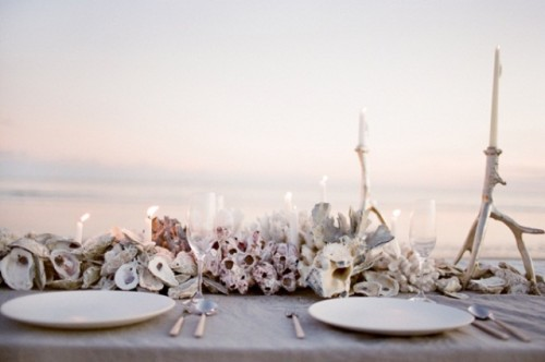 a neutral beach wedding tablescape with lots of corals, seashells, neutral candles and porcelain
