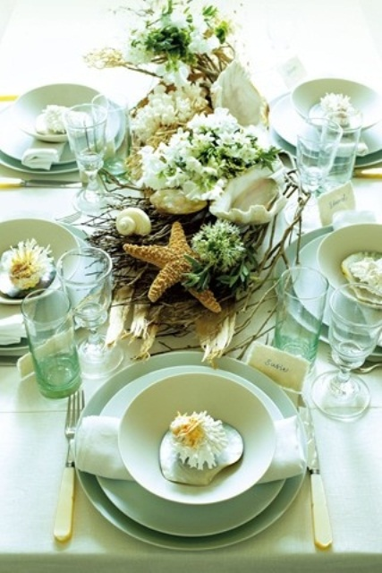 a light green beach wedding table with green porcelain, glasses, a centerpiece of green blooms, twigs and a starfish
