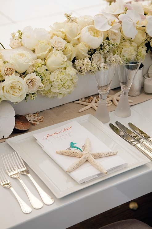 a neutral wedding tablescape with white blooms, seashells and starfish, square plates and a starfish on top