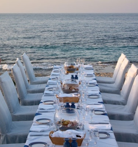 a simple and romantic beach wedding table with blue vases, plates, wooden boxes for bread and neutral napkins