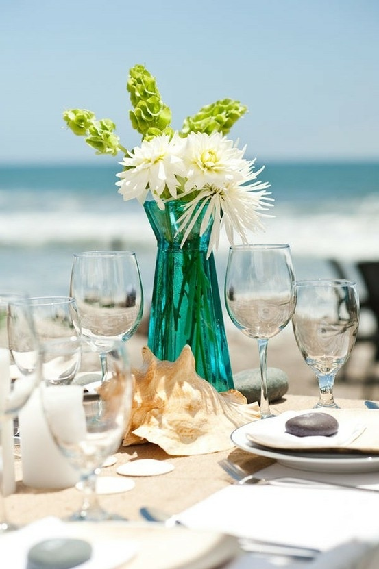 a beach wedding table with an oversized shell, a turquoise vase with neutral blooms, white candles and pebbles on the plates