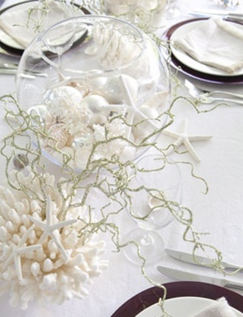 an all white beach wedding table with corals, driftwood, seashells in a glass globe and dark plates
