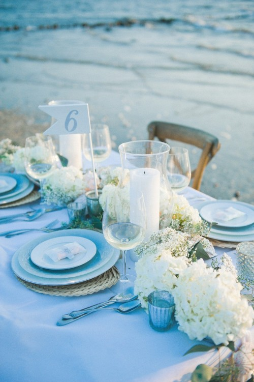a beautiful light blue and neutral beach wedding tablescape with neutral blooms, blue plates and glasses and woven placemats