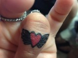 a red heart and wing tattoo on the top part of the ring finger is a bold and lovely idea to rock