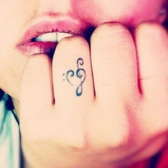 a treble clef heart shaped tattoo on the ring figer is a lovely idea for those who love music
