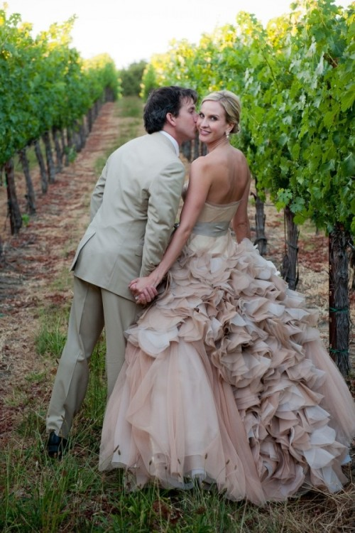 a dusty pink strapless wedding ballgown with a ruffled skirt and a silver sash for a chic vineyard wedding