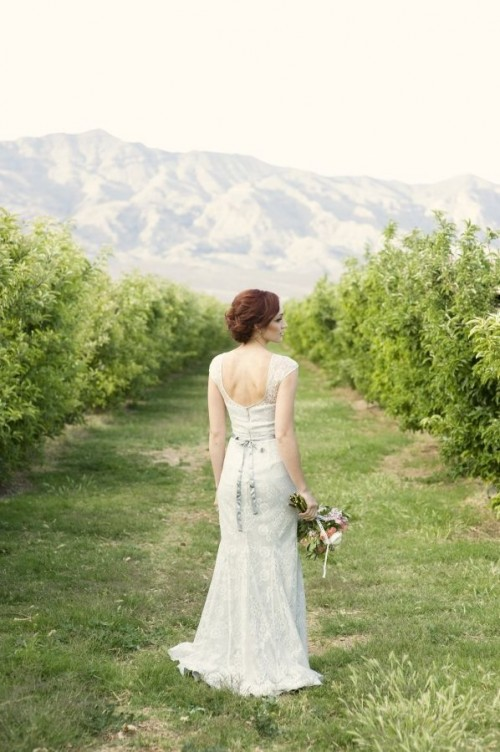 a white lace sheath wedding dress with a cutout back, a floral sash will highlight all your curves at its best