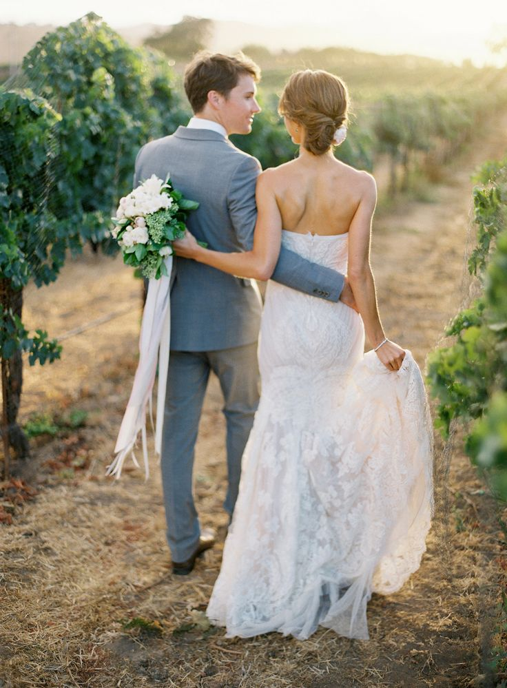 a white lace strapless mermaid wedding dress with a train is a stylish and very girlish idea for a vineyard bride