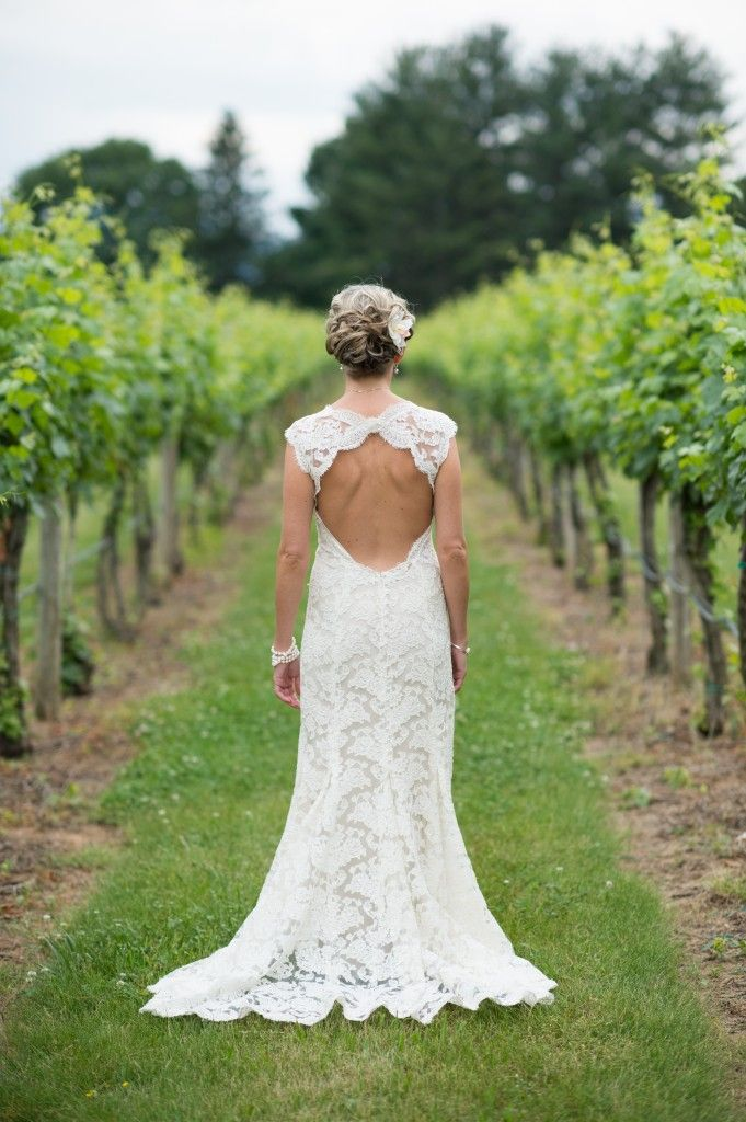 a lace sheath wedding dress with no sleeves, a cutout back and a high neckline plus a train
