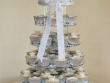 a white wedding cake and matching cupcakes in silver liners plus a large bow with rhinestones