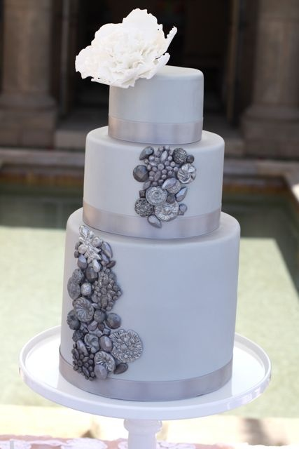 a white winter wedding cake decorated with silver edible elements and a large white bloom on top