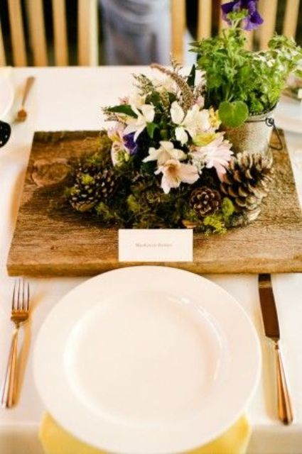 a wedding centerpiece of a board with moss, blooms, pinecones, a bucket with greenery is very whimsy and creative