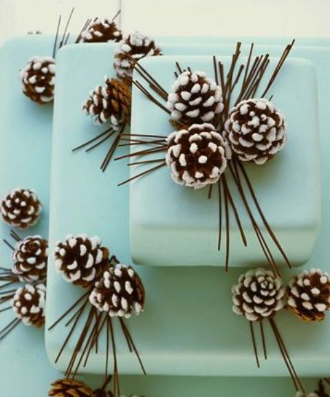 a light blue square wedding cake with snowy pinecones is a chic and bold dessert idea for your winter wedding