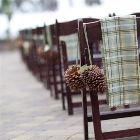 oversized pinecones on ribbons and green plaid blankets for marking chairs at the ceremony space and to keep guests warm