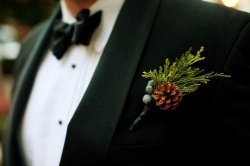 a pinecone, greenery and berries wedding boutonniere is a lovely accessory for a groom or groomsmen in winter
