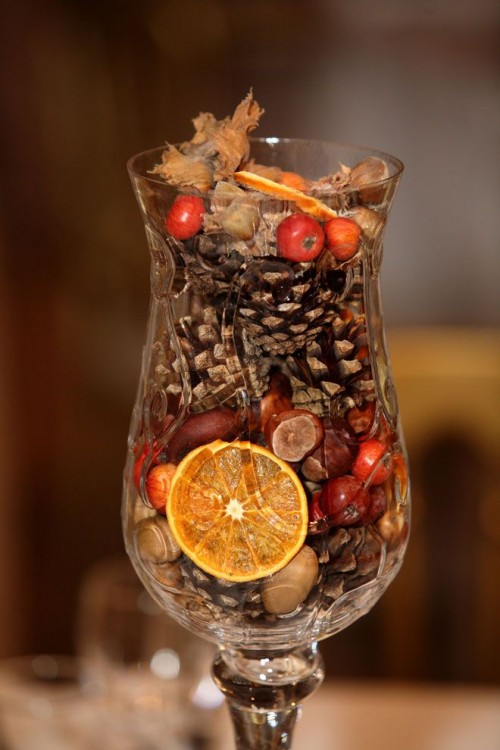 a tall glass with berries, pinecones, dried citrus, nuts and wood is a lovely wedding centerpiece