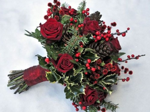 a bold winter wedding bouquet of burgundy blooms, berries, foliage and evergreens is a bold and lovely option