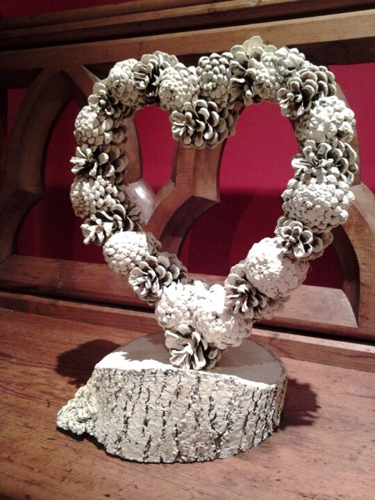 a snowy pinecone wreath on a wooden stand is a stylish decoration for a winter wedding