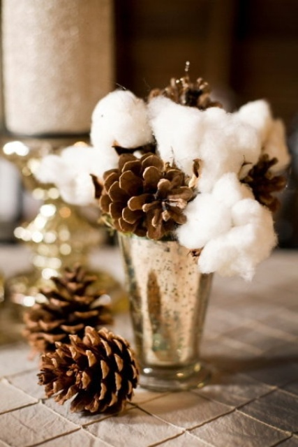 a refined winter wedding decoration of a mercury glass vase, cotton and pinecones is a lovely and chic idea