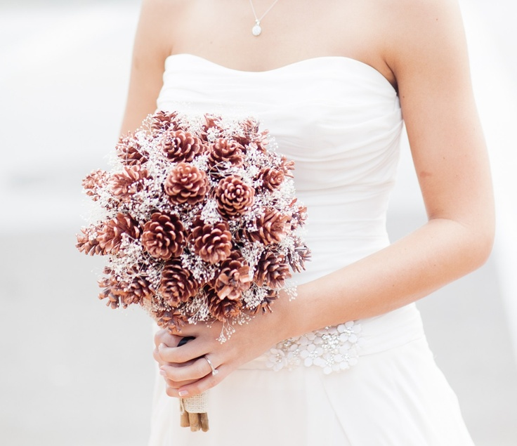 a pinecone wedding bouquet with silver touches is a cool idea of a non traditional arrangement to rock