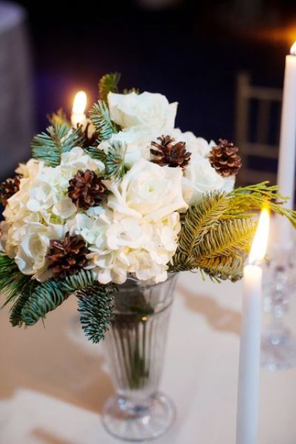 a winter wedding centerpiece of a glass vase, evergreens, white blooms and pinecones is amazing and easy to DIY