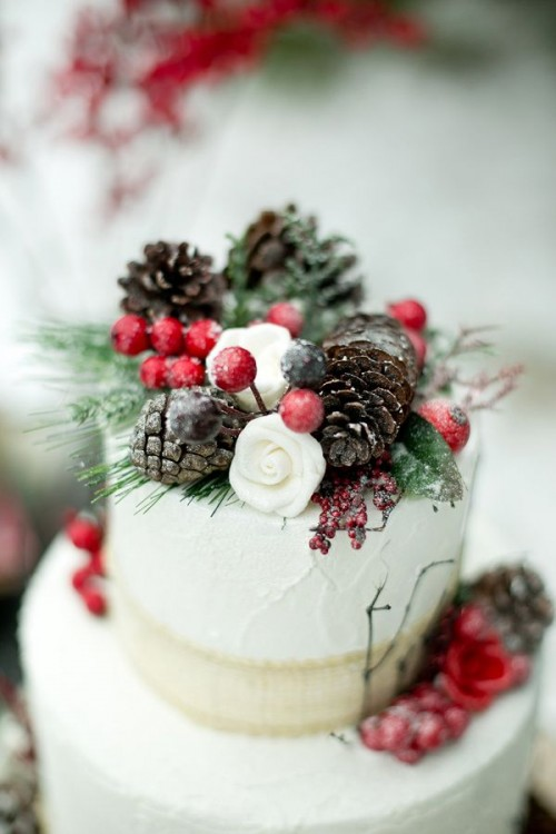 a white textural wedding cake with berries, pinecones, white blooms and greenery is a lovely winter-inspired wedding dessert