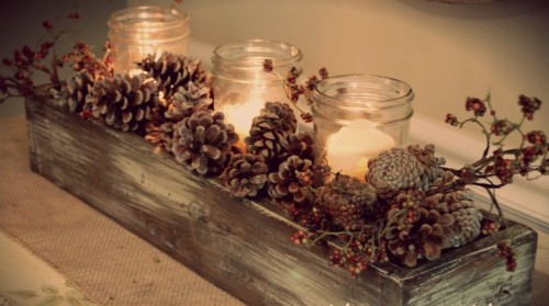 a rustic winter wedding centerpiece of a wooden box, pinecones, berries and candles in jars