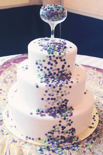 a white wedding cake covered with colorful confetti and with a glass with confetti as a topper is all fun