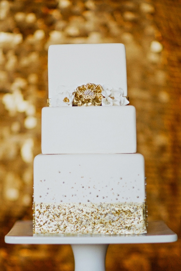 a white square wedding cake with gold glitter and beads, with white and gold sugar blooms is a very glam and cool idea