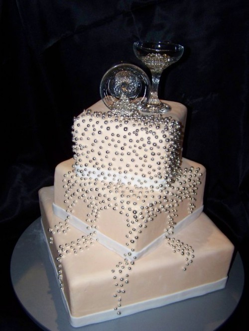 a tan square wedding cake with silver beads and champagne glasses on top is a chic and shiny idea