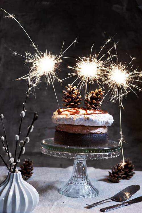 a small naked wedding cake with pinecones, caramel drip on top and some sparklers is a lovely idea for a NYE wedding