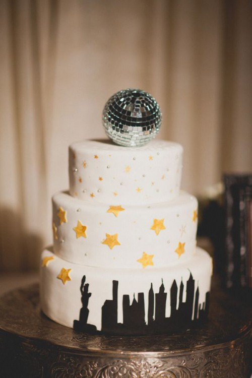a NYE wedding cake with a city look, some stars, beads and a disco ball on top is lovely