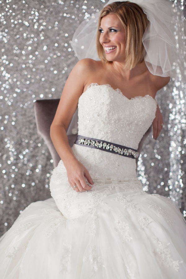 a strapless lace embellished mermaid wedding dress with an embellished sash and a veil is very girlish and glam