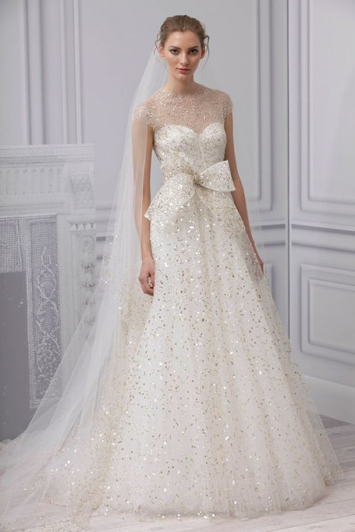 a fully embellished A-line wedding dress with an illusion neckline, cap sleeves and a large bow is a chic idea to rock