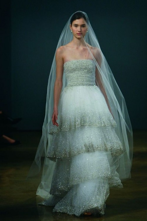 a strapless sheath wedding dress with a layered skirt with gold sparkles along the edge and a long veil is wow