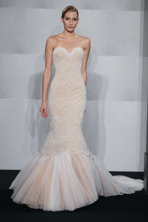 a white and peachy mermaid wedding dress with a strapless neckline and embellishments and a long train is a sexy idea