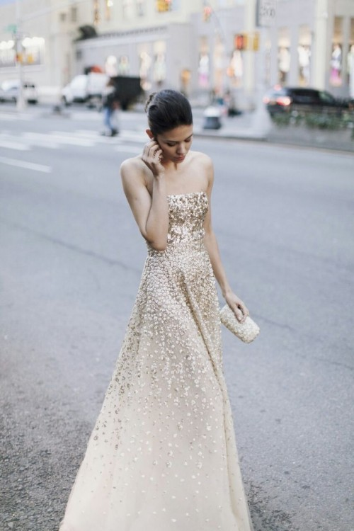 a strapless ivory and gold sequin A-line wedding dress with an ombre effect and a glam embellished clutch